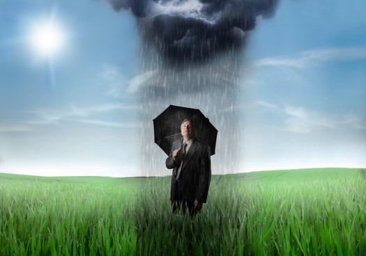 Sad senior businessman on a green meadow with downpour over him